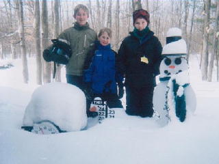 Funk boys standing next to the snowman.