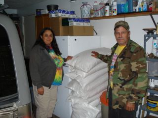 Tom and Dee Cramer standing in front of the 500 pounds of corn they donated to help feed the wildlife seen on the Snowman Cam. 8-12-08