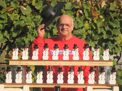 Italian woodworker and craftsman, Richard Guccini, standing with his snowman creations.